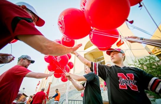 Brendon Nelson, 12, hands out balloons to Husker fans before a Nebraska football game against Illinois outside Memorial Stadium in Lincoln. KRISTIN STREFF/Lincoln Journal Star
