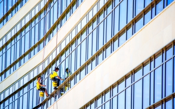 """Window washers Vincent Matejka (left) and Tim Blundell from Roy's Window Service dangle from ropes as """"just part of the job"""" at the Assurity Life Insurance building along Antelope Parkway in Lincoln. KRISTIN STREFF/Lincoln Journal Star"""