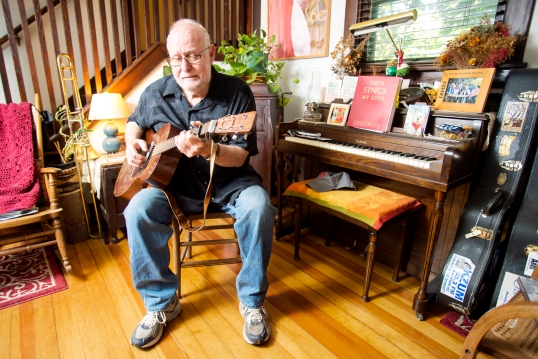 "Musician and author John Walker practices ""Buckets of Rain"" by Bob Dylan after recently recovering from shoulder surgery in his home in Lincoln. KRISTIN STREFF/Lincoln Journal Star"