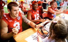 Nebraska quarterbacks Taylor Martinez (from left), Ron Kellogg III, and Tyson Broekemeier sign autographs for young fan Grace Schafer, 4, of Lincoln during Nebraska Football Fan Day at Memorial Stadium in Lincoln. KRISTIN STREFF/Lincoln Journal Star