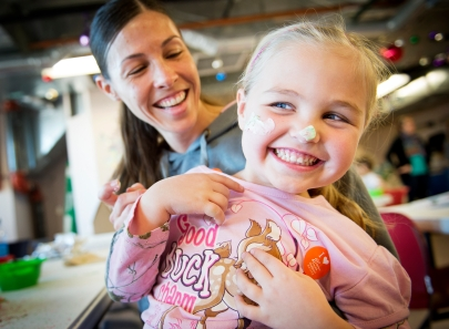 """Ashlyn Erickson, 4, of Waverly tries to wiggle away from her mom, Angela, after being """"frosted"""" during the Candy House Funshop at the Lincoln Children's Museum. KRISTIN STREFF/Lincoln Journal Star"""