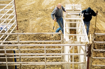 UNL Rodeo Club members Braden Rieker (left) and Jordan Burhoop pack dirt along a shoot to steady it in preparation for the PRCA Championship Rodeo at the Pershing Center. KRISTIN STREFF/Lincoln Journal Star