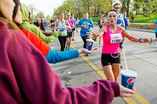 Rose Sutton of Wahoo, Neb. reaches for a cup of water from a volunteer during the Lincoln National Guard Marathon near the five-mile mark along 48th Street. KRISTIN STREFF/Lincoln Journal Star