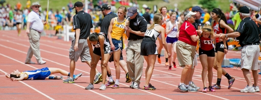 Collapsed and weary runners are helped off the track after competing in the Class B 3,200-meter run finals on the opening day of the state track and field championships at Omaha Burke Stadium. KRISTIN STREFF/Lincoln Journal Star