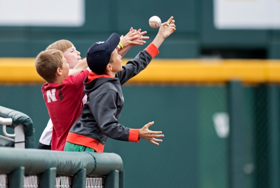 Young Husker fans reach for a foul ball along the third baseline during a semifinal game against Michigan in the Big 10 baseball tournament at TD Ameritrade Park. KRISTIN STREFF/Lincoln Journal Star