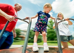 Leyna, 2, gets a spin on the merry-go-round from her parents Mitchell and Karri Ahlschwede at the playground at Porter Park. KRISTIN STREFF/Lincoln Journal Star