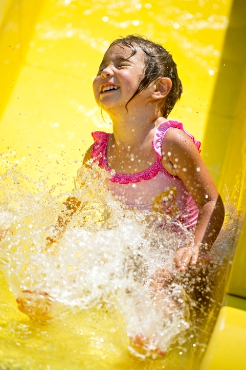 Sophia Ybarra, 3, of Lincoln crashes into the water at the bottom of the slide at the Woods Sprayground. After a week of comfortably cooler temperatures, families flocked to the city's pools to beat the return of near 100-degree heat. KRISTIN STREFF/Lincoln Journal Star