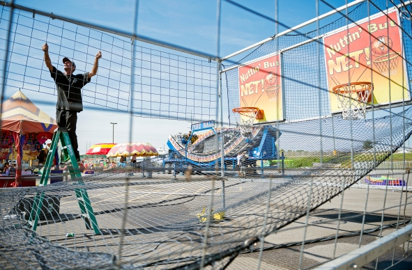 Preparing for opening day of the Lancaster County Super Fair, a carnival employee sets up the Nuttin' But Net carnival game outside the Lancaster Event Center. KRISTIN STREFF/Lincoln Journal Star
