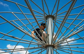 Preparing for opening day of the Lancaster County Super Fair, ride technician Vinny Roman sets up the frame for the awning over the boat ride outside the Lancaster Event Center. KRISTIN STREFF/Lincoln Journal Star