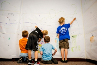 Luke Rimpley (from left), Landon Holmberg, Liam Tvrdy, and Heath Carlson draw on the paper-covered walls during Doodle Design camp at the Lincoln Children's Museum. KRISTIN STREFF/Lincoln Journal Star