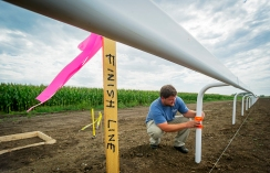 Lincoln Race Course employee Jared Schwedy checks the level of one of the rail posts near the dirt racetrack's finish line marker at the Lincoln Race Course. KRISTIN STREFF/Lincoln Journal Star