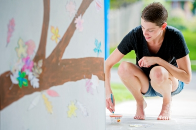 Local artist Ann Williams paints leaves onto doors for the Doorways to Hope community art project at her home in east Lincoln. The doors will be strung together to form a 24-foot wall on which the community can paint their own leaves during the Doorways to Hope Day celebration next weekend. KRISTIN STREFF/Lincoln Journal Star