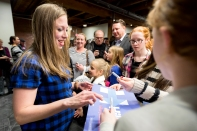 Chelsea Clinton, daughter of democratic candidate Hilary Clinton, signs an campaign poster for supporters while campaigning for her mother at Fuse Coworking in the Haymarket. KRISTIN STREFF/Journal Star