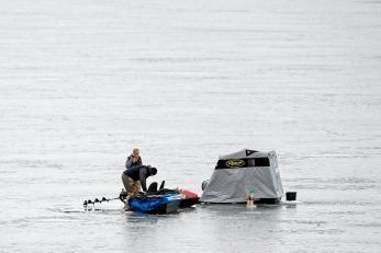 A pair of ice fishermen adjust their shelter while enjoying a quiet morning on the lake at the Yankee Hill Wildlife Management Area. KRISTIN STREFF, Journal Star