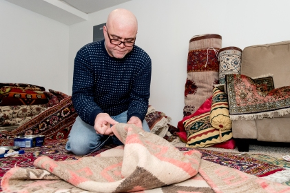 Using a long needle and sturdy thread, Ramin Shafaian repairs and restores a Navajo rug in his basement at his Lincoln home. KRISTIN STREFF, Journal Star