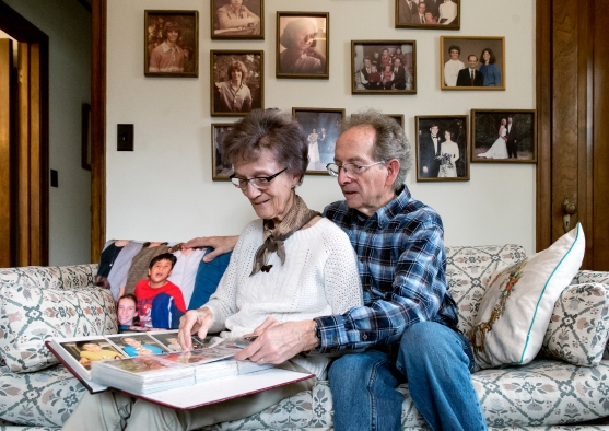 Rosemary and Mel Thornton flip through a family photo album in their home office at their home in central Lincoln. KRISTIN STREFF, Journal Star