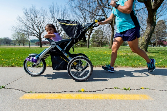 A runner and her young companion navigate the cracks in the concrete during a morning jog along the Billy Wolff Trail near Holmes Lake. A repair is planned for this portion of the trail. KRISTIN STREFF, Journal Star