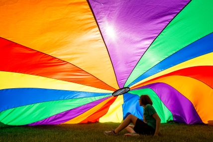 St. Mary's eighth grader Elle Marroquin laughs as she gets caught under a parachute during their school field day on the green space on Centennial Mall. KRISTIN STREFF, Journal Star