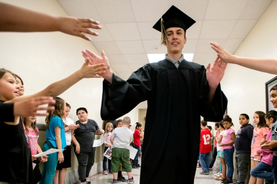 Lincoln Southeast graduate and Hartley Elementary alum Joshua Erb collects high fives from young students cheering him on during a graduate celebration at Hartley Elementary. KRISTIN STREFF, Journal Star