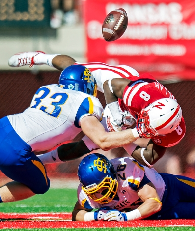 Nebraska running back Ameer Abdullah (8) fumbles after being hit by South Dakota State linebacker T.J. Lally (33) and defensive back Drew Kreutzfeldt (26) during the first quarter at Memorial Stadium. KRISTIN STREFF/Lincoln Journal Star